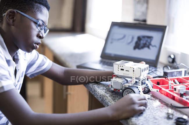 Scolaro con il computer portatile in classe di robotica — Foto stock