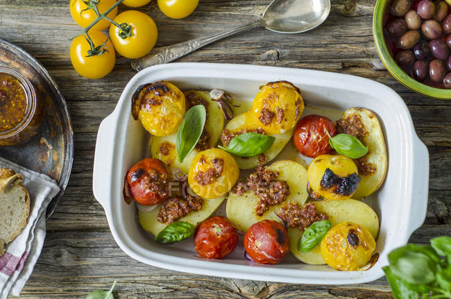 Grilled potatoes with tomato pesto, tomatoes and basil leaves in baking dish on wood — Stock Photo