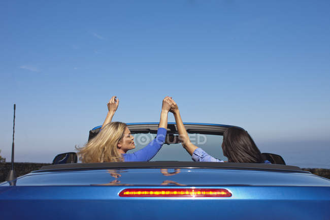Two women hand in hand in a convertible — Stock Photo