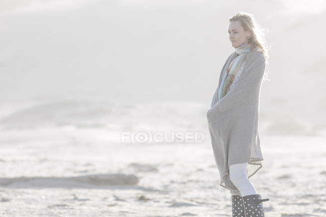 Young woman standing on the beach — Stock Photo