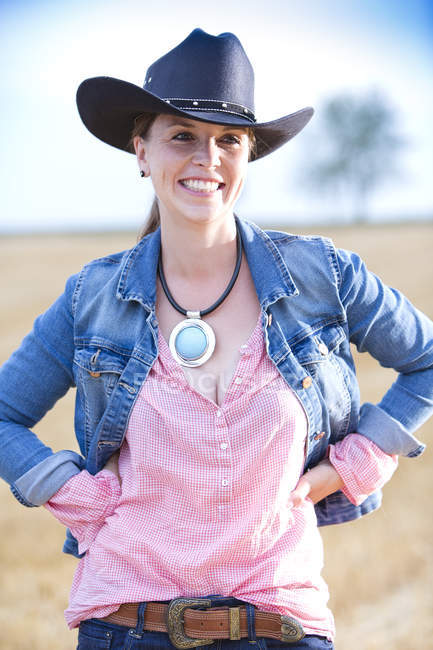 Portrait of smiling young woman wearing cowboy hat and jeans jacket — Stock Photo