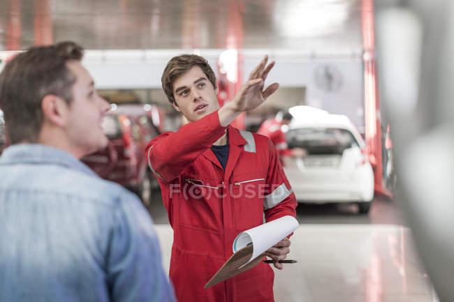 Car mechanic and customer in repair garage — Stock Photo