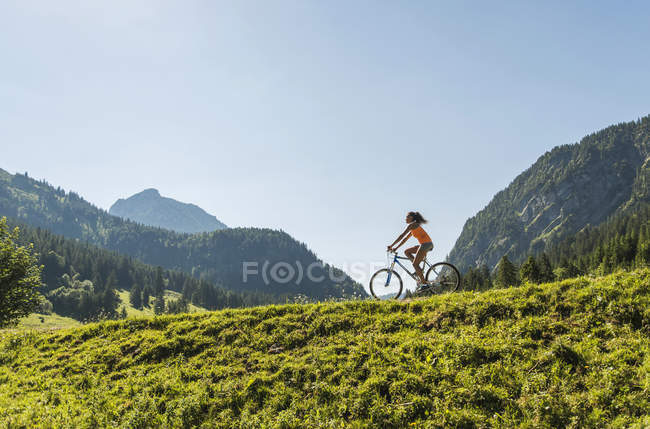 Austria, Tyrol, Tannheim Valley, young woman on mountain bike in alpine landscape — Stock Photo