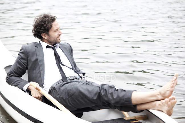 Empresário no terno relaxante em canoa — Fotografia de Stock
