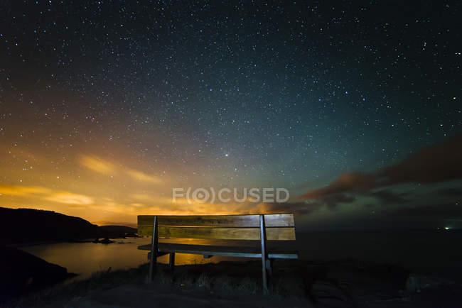 España, Ortigueira, Loiba, banco bajo cielo estrellado con rayo azul - foto de stock