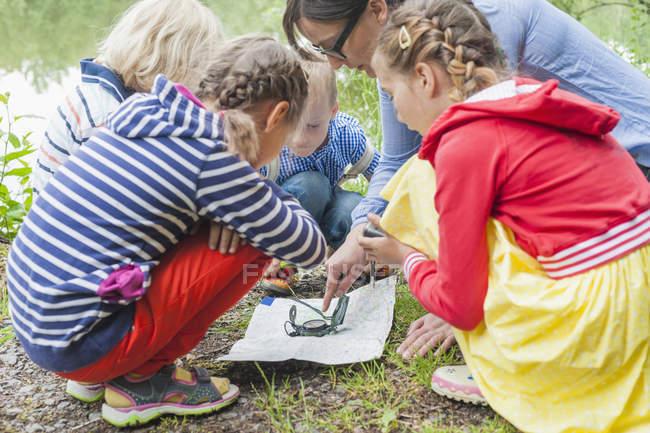 Дети и учителя, научиться использовать компас и карта — стоковое фото