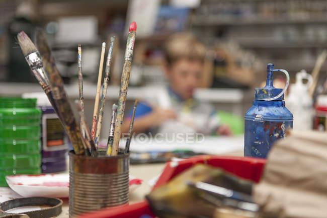 Pennelli in piedi in una lattina in una scuola di arti — Foto stock