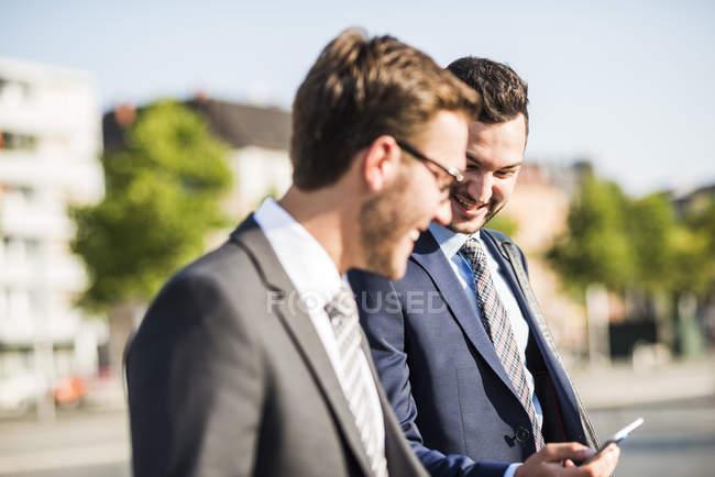 Due giovani uomini d'affari che camminano in città, guardando il cellulare — Foto stock