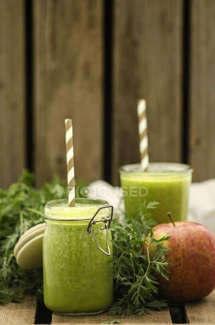 Batido de maçã cenoura, preservando a jarra com canudos a beber — Fotografia de Stock