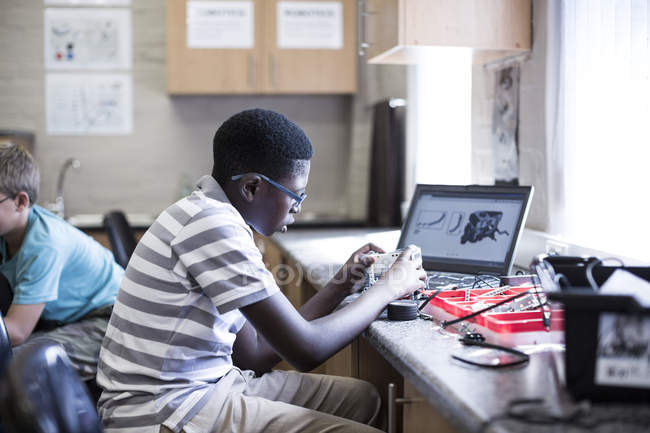Schoolboys working with laptop in robotics class — Stock Photo