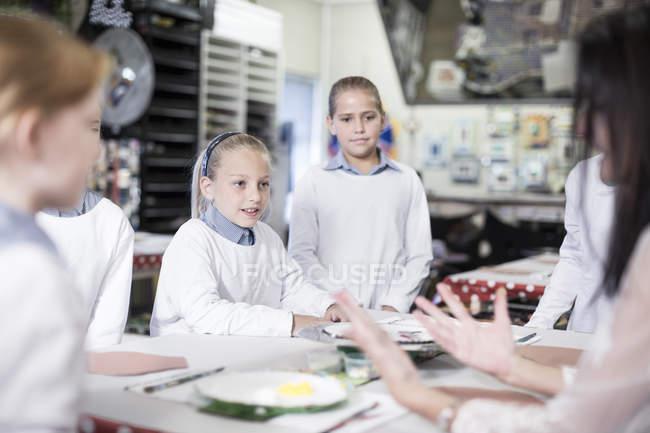 Capretti che studiano con insegnante nel codice categoria di arte a scuola — Foto stock