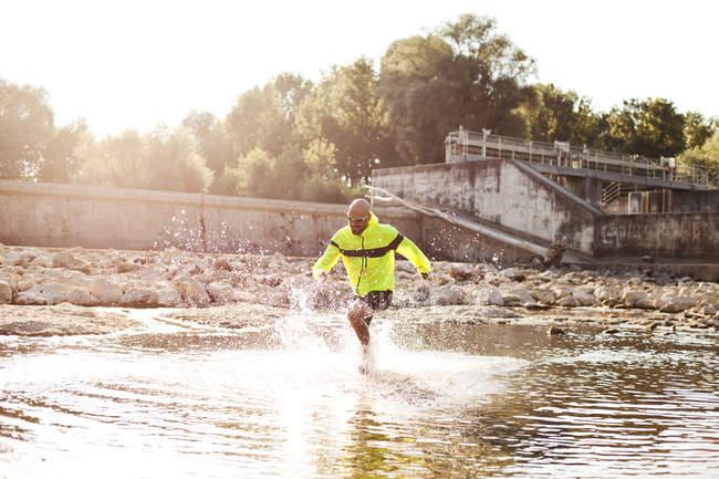 Homme en tenue de sport courant dans l'eau — Photo de stock