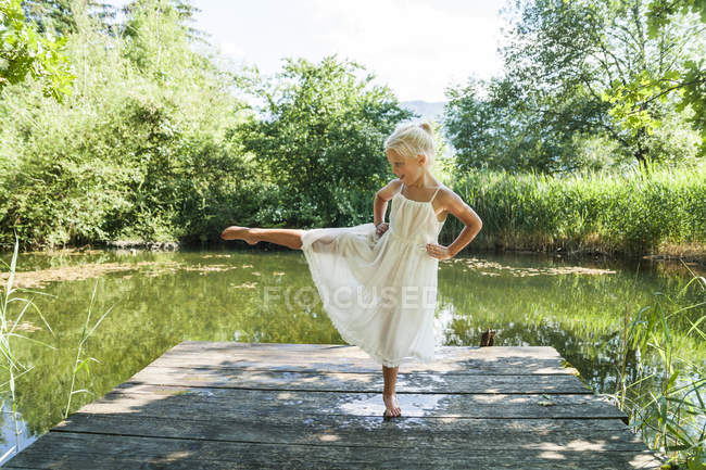 Girl standing on one leg on jetty — Stock Photo