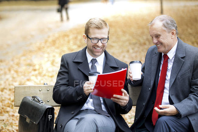 Businessmen sitting with document on park bench — Stock Photo