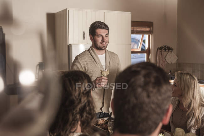 Young man making a speech to friends at dinner table — Stock Photo