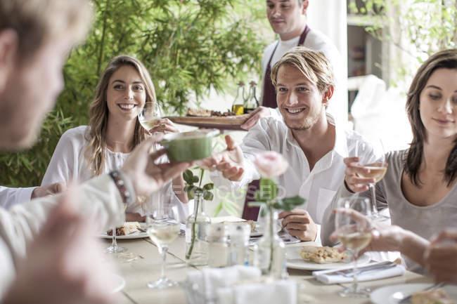 Amigos almorzando juntos en el restaurante, sentados afuera - foto de stock