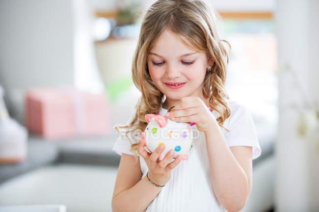 Chica lanzando monedas en hucha - foto de stock