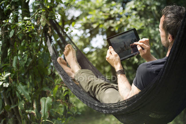 Расслабленный человек лежит в гамаке с цифровой таблеткой — стоковое фото