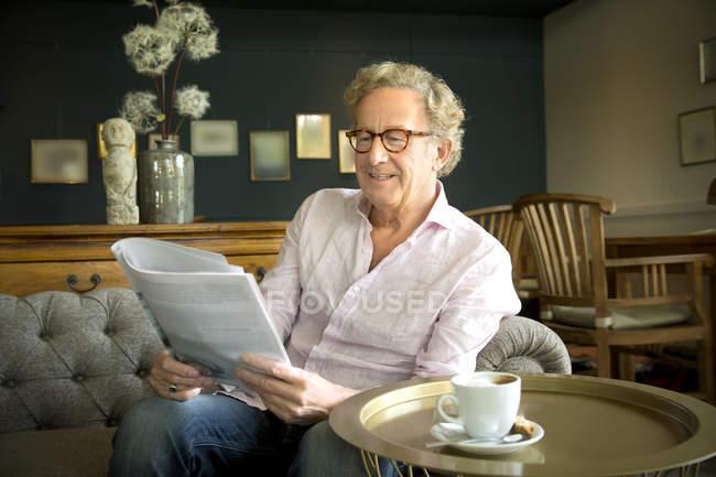 Uomo anziano sorridente in salotto lettura rivista — Foto stock