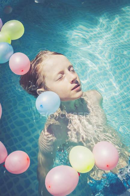 Garoto na piscina rodeada por balões flutuando na água — Fotografia de Stock