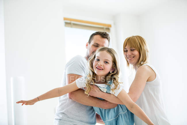 Parents playing with daughter, pretending to fly at home — Stock Photo