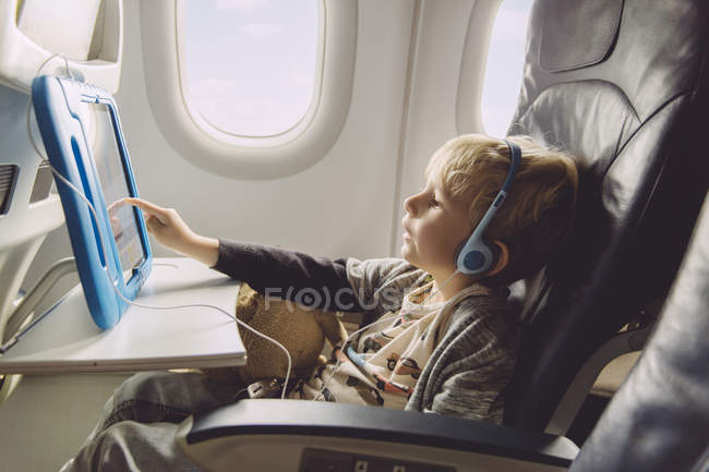 Little boy sitting on an airplane watching something on digital tablet — Stock Photo