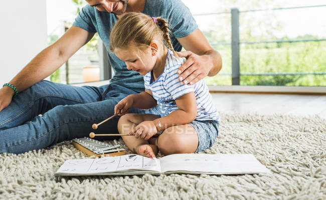Father with daughter on rug playing musical instrument — Stock Photo