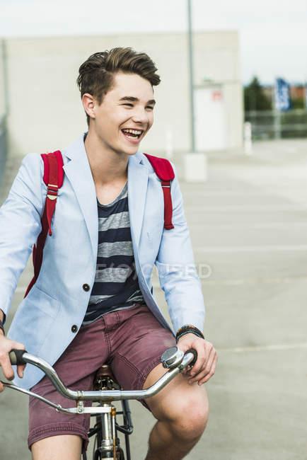 Heureux jeune homme à vélo sur le niveau de stationnement — Photo de stock