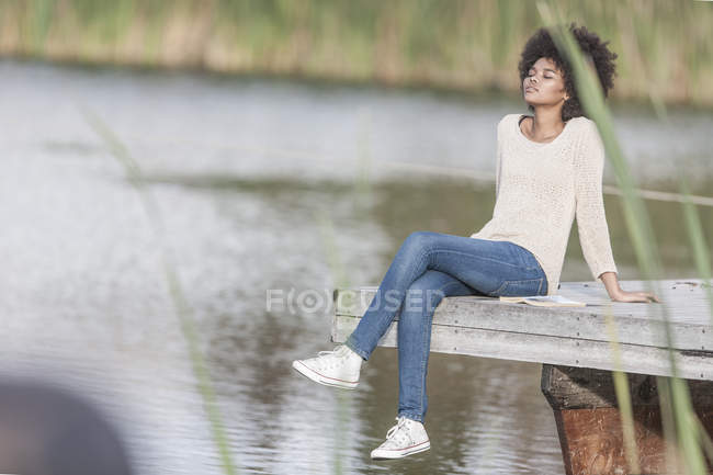 Woman relaxing on a jetty at lake — Stock Photo