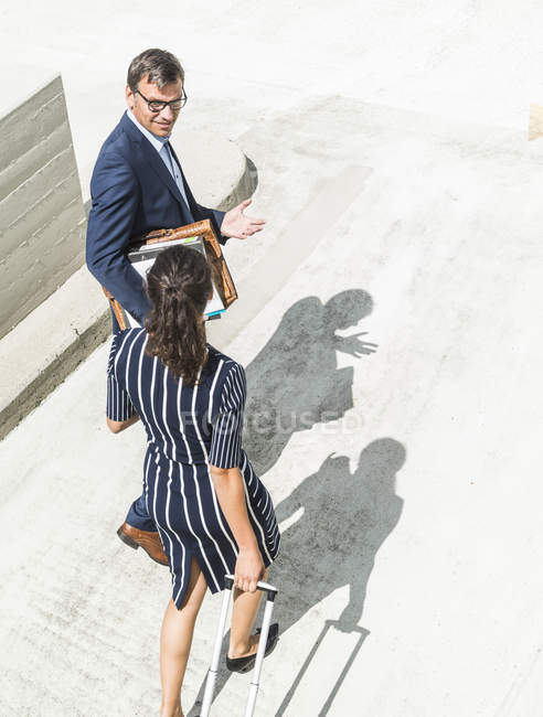 Mature businessman and young woman with trolley walking in yard — Stock Photo
