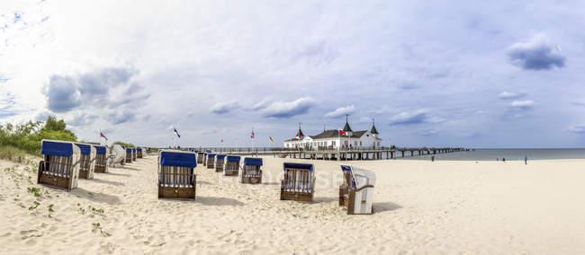 Німеччина, Ahlbeck, вид на море міст з капюшоном пляжні шезлонги на пляжі на передньому плані — стокове фото