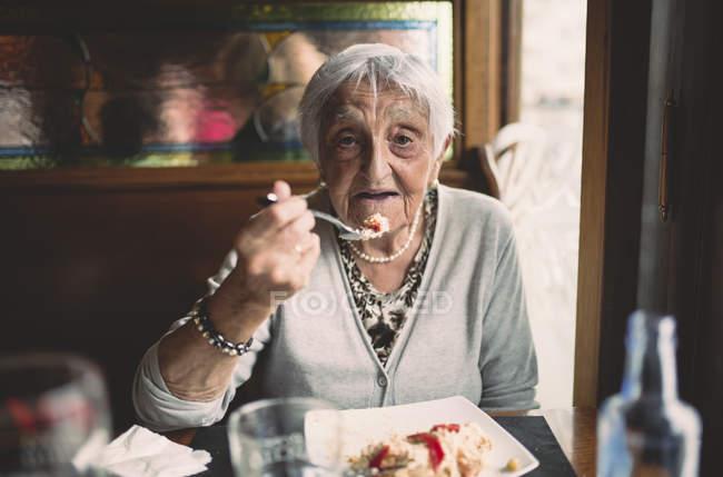 Portrait of smiling senior woman eating in restaurant — Stock Photo