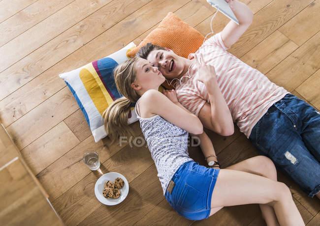 Feliz joven pareja tumbada en el piso compartiendo tableta digital - foto de stock
