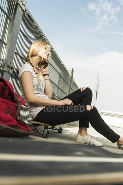 Adolescente, assis sur une planche à roulettes parler sur téléphone portable — Photo de stock