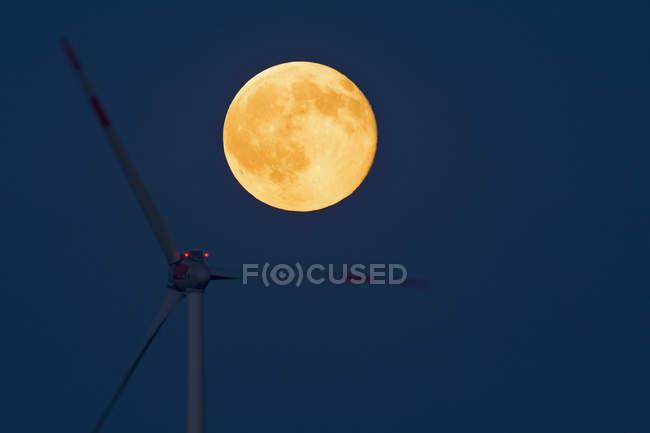 Alemania, salida de luna llena con rueda de viento en primer plano - foto de stock