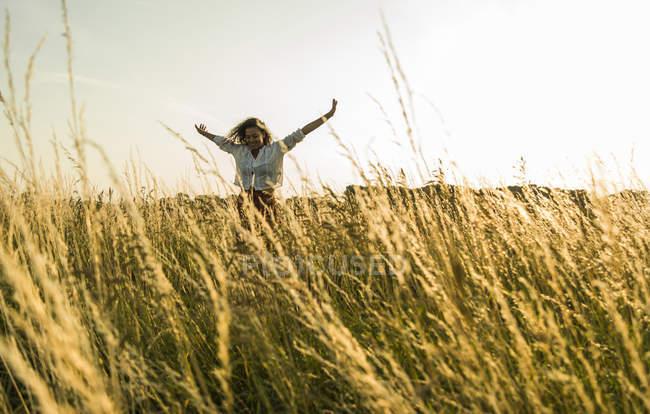 Junge Frau mit ausgestreckten Armen in Bereichen mit hohen grass — Stockfoto