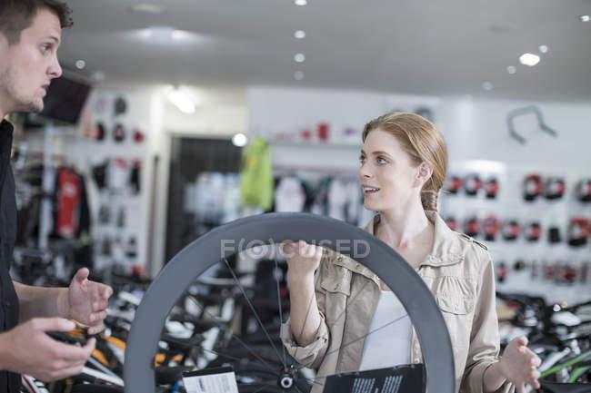 Giovane venditore e cliente guardando le biciclette — Foto stock