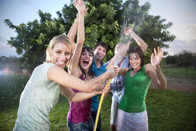 Cinque amici che spruzzano acqua in giardino di giorno — Foto stock
