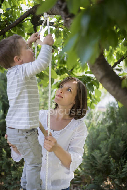 Mutter hilft ihrem kleinen Sohn eine Strickleiter erklimmen — Stockfoto