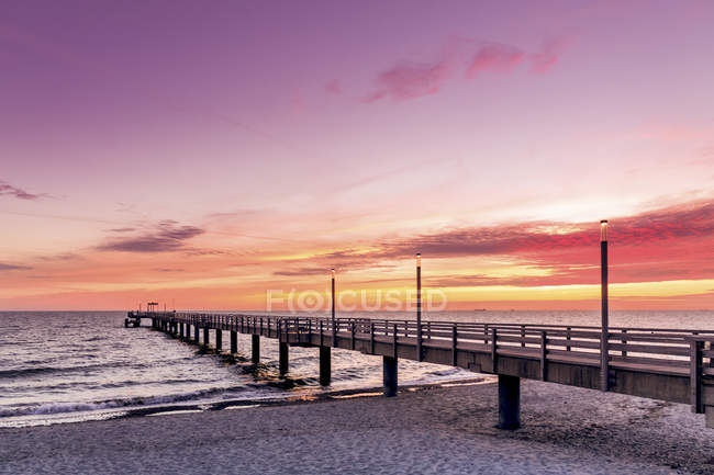 Germany, Heiligendamm, sunrise at pier over water — Stock Photo