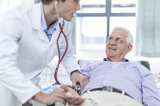 Arzt überprüft Blutdruck eines älteren Patienten — Stockfoto