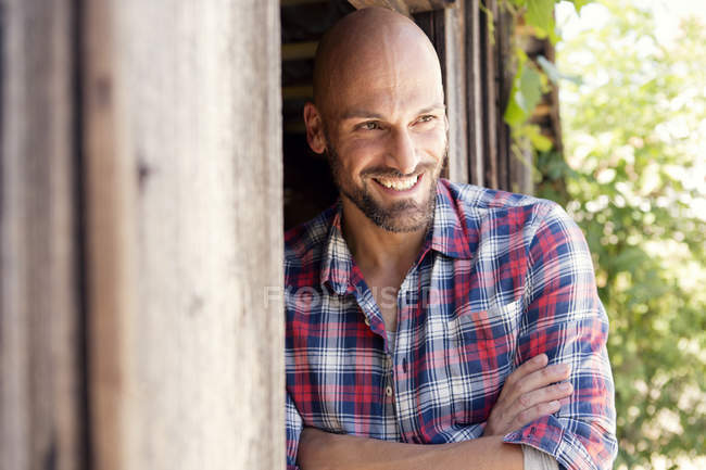 Portrait of smiling man with crossed arms wearing checked shirt — Stock Photo