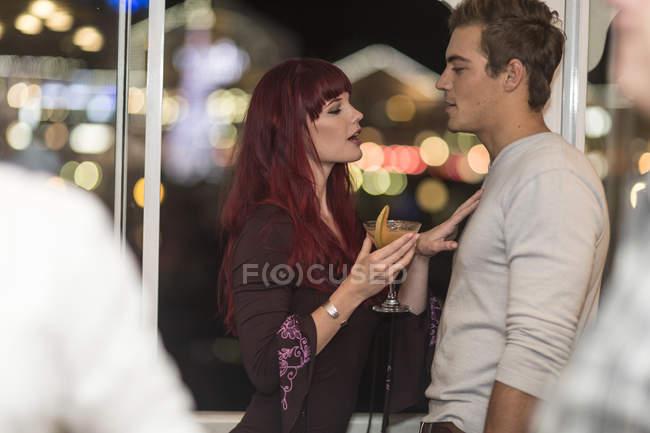 Jovem com copo de coquetel flertando com o jovem — Fotografia de Stock