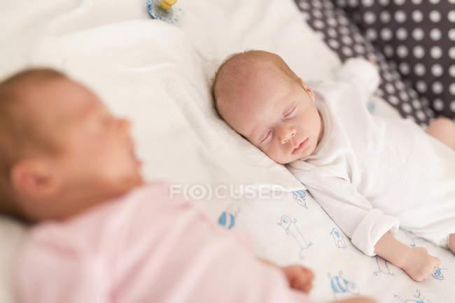 Спящая мило новорожденных близнецов в постели — стоковое фото