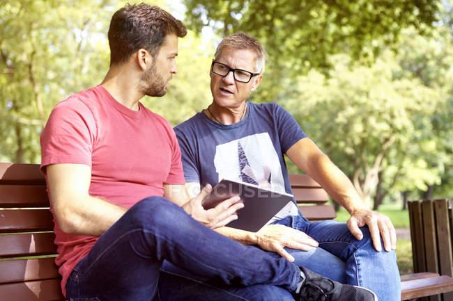 Два мужчины, сидя на скамейке в парке с цифрового планшета — стоковое фото