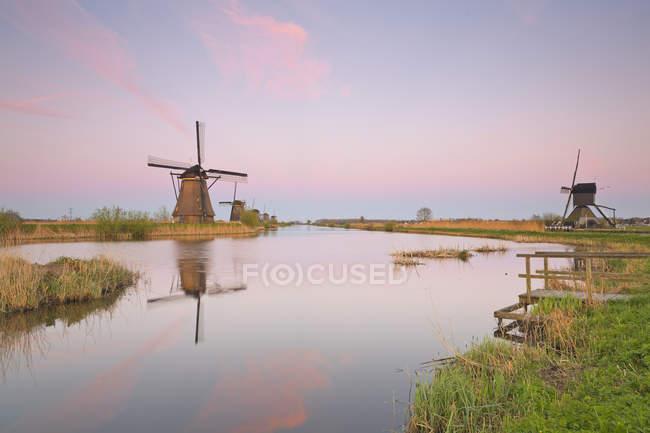 Países Bajos, Kinderdijk, Kinderdijk molinos de viento en el crepúsculo - foto de stock