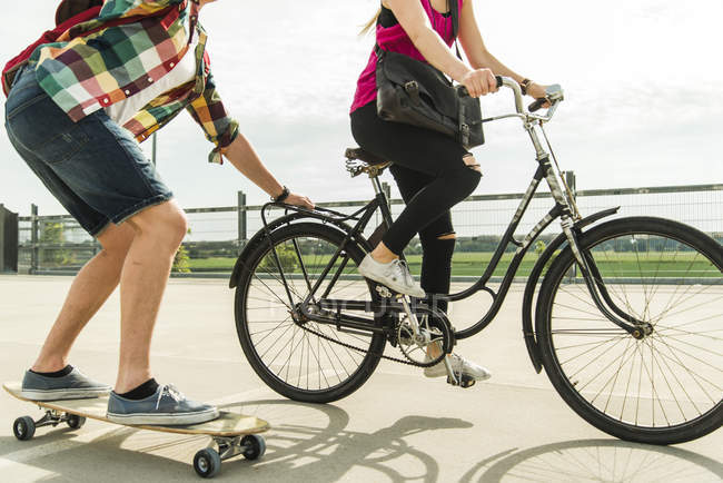 Young couple riding bicycle and skateboard — Stock Photo