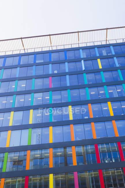 Moderno edificio de oficinas, fachada de vidrio colorido durante el día - foto de stock