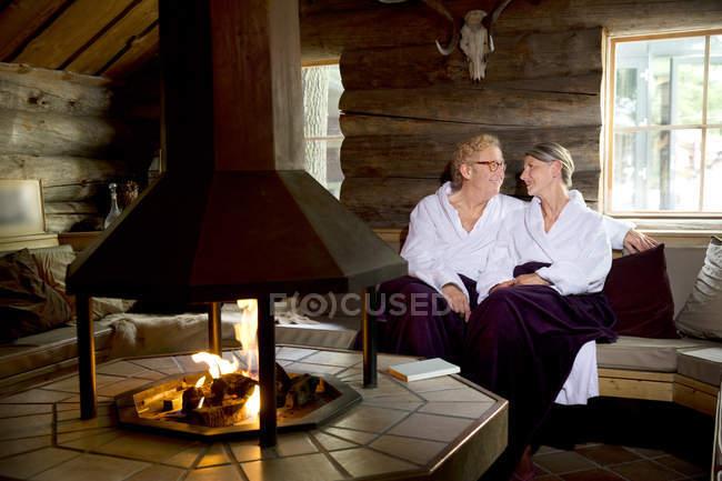 Sorrindo casal sênior vestindo roupões de banho sentado na lareira — Fotografia de Stock