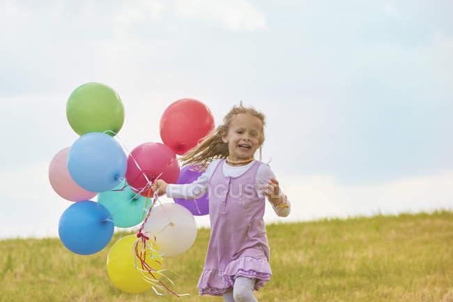 Kleines Mädchen mit Luftballons auf einer Wiese — Stockfoto